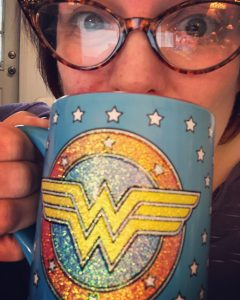 Michelle sipping coffee from a Wonder Woman mug